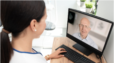 Woman doctor talking to an older patient through a laptop